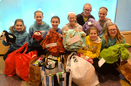 Inside Peyton Manning Children's Hospital, the girls in Crafts for Courage hold their gift of 31 blankets. Left to Right: Allison Hendrix, Grace Reynolds, Sydney Proctor, Maggie McAndrews, Rebecca Davidson, Abigail Gift, Makaiah Haberkorn and Olivia Beardslee.