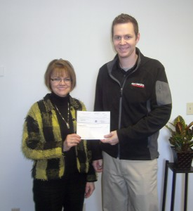 Debbie Laird, Janus Developmental Services vice president of development and transportation, accepts a check from Brian Peterson, branch manager of W.W. Grainger in Indianapolis. (Photo submitted)