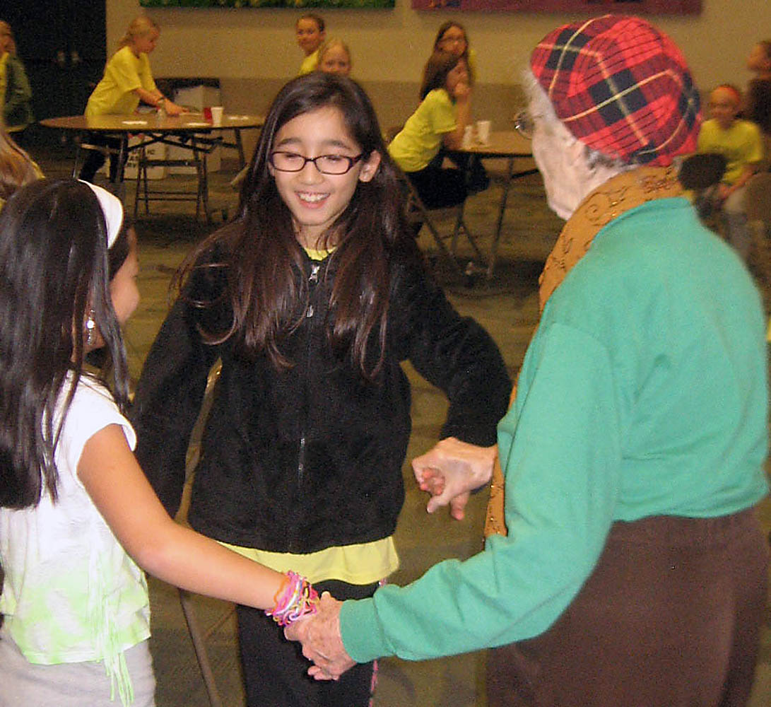Oak Trace Elementary students Claire Davis and Grace Stewart dance with a Sanders Glen resident. (Photo provided by Tenna Pershing)