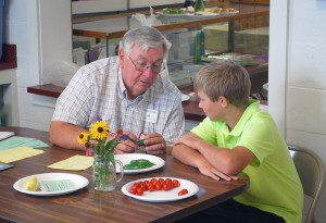 Gardening Judge Jim Barbour talks to 4-H'er Jeremiah Witek about his jalapeño peppers during the 2012 Hamilton County 4-H Fair. (File photo by Robert Herrington)