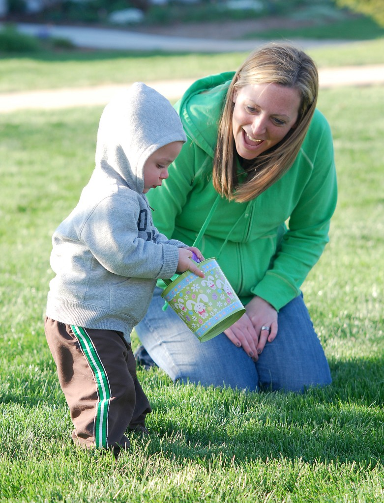 Patty Wittmann encourages Brady Wittmann, 15 months, as he collects eggs. (File photo by Robert Herrington)