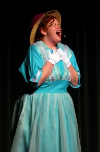 """Dolly Levi (Anna Christianson) sings """"Before the Parade Passes By"""" and asks for her late husband's permission to move on and marry Horace Vandergelder."""