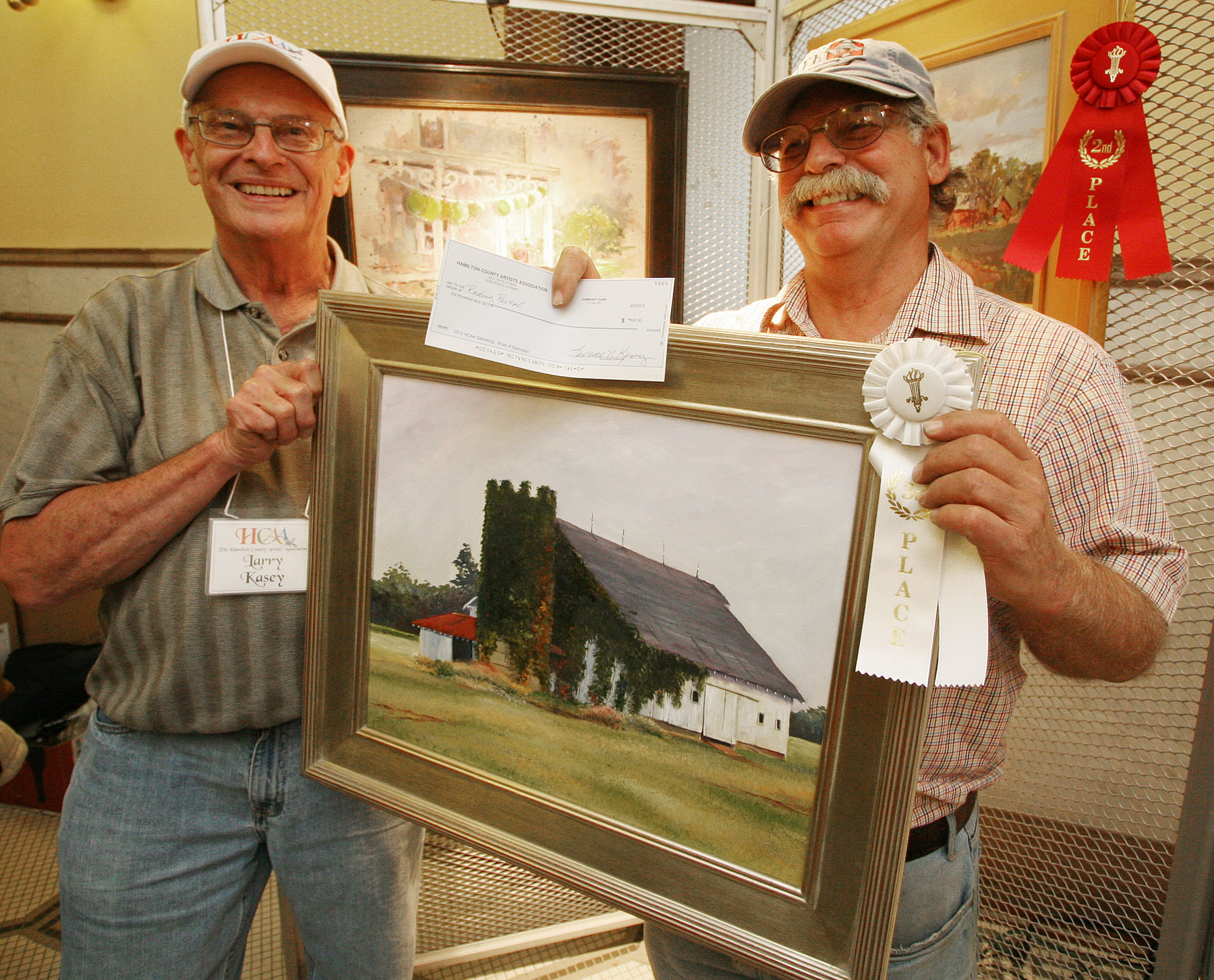 Larry Kasey, HCAA treasurer and Gathering chairman, left, recognizes Rodney Reveal as winner of the $600 Prize of Distinction during the HCAA's fourth annual Gathering of plein air painters. (photo submitted)
