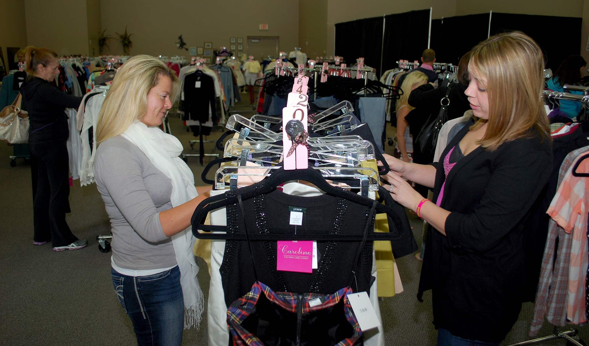 Yana Dess, left, and Christine Daviduke look at a rack of clothes at the Pink Label Event.
