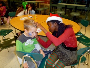 "Oak Trace Elementary kindergarten Student Johnny Ewing has his face painted by Westfield High School Executive Committee member Tolu Odimayomi. The executive committee hosted the ""Breakfast With Santa"" on Dec. 10, 2012, which provided more than 150 elementary students with crafts, face painting, food and the opportunity to meet with Santa and Mrs. Claus. (Photo provided)"