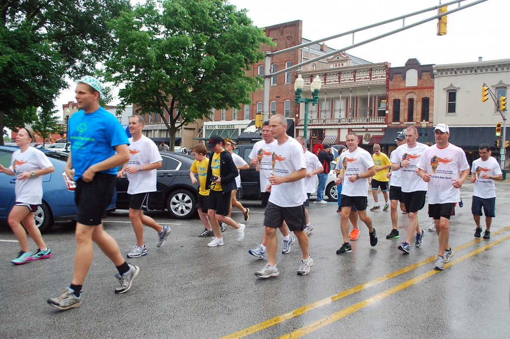 Local law enforcement officers and Special Olympics athletes circle the downtown Noblesville Square at the conclusion of the annual Torch Run.