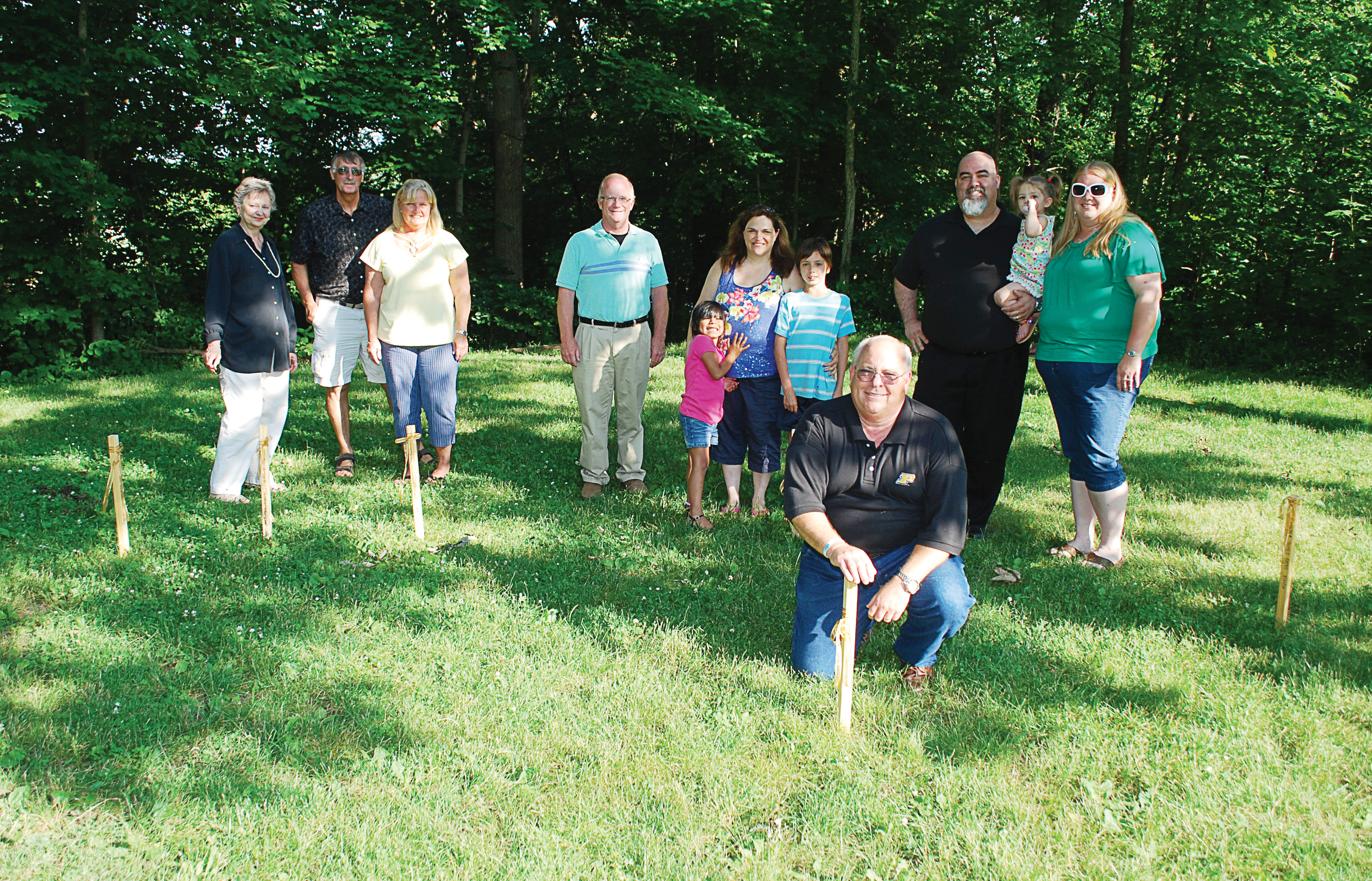 From left: Mary Sue Rowland, Bill and Sue Childs, Garry Warren, Ashley, Suzanne and Christian Brooks, Kirk Forbes and Jim, Madeline and Brandi Bates place temporary wooden stakes in the location of the Angel of Hope Memorial Garden to kick off its fundraising efforts. (Photos by Robert Herrington)