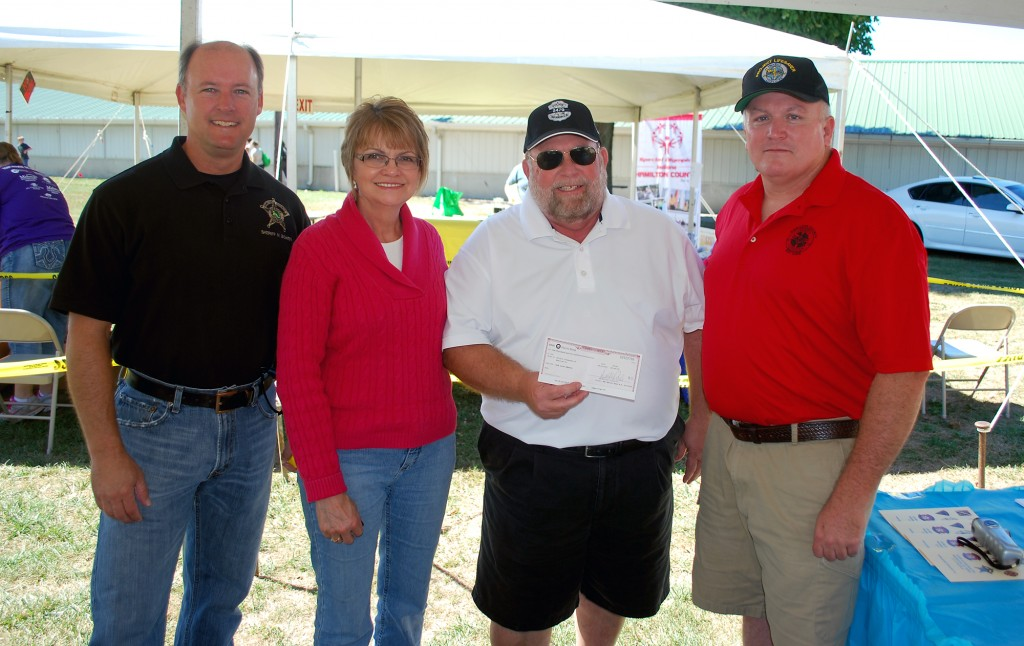 Debbie and Jim Laird, center, present a $1,000 check on behalf of the Jake Laird Memorial Fund to Sheriff Mark Bowen, left, and David McCormick for the Hamilton County Project Lifesaver program. (Photo by Robert Herrington)