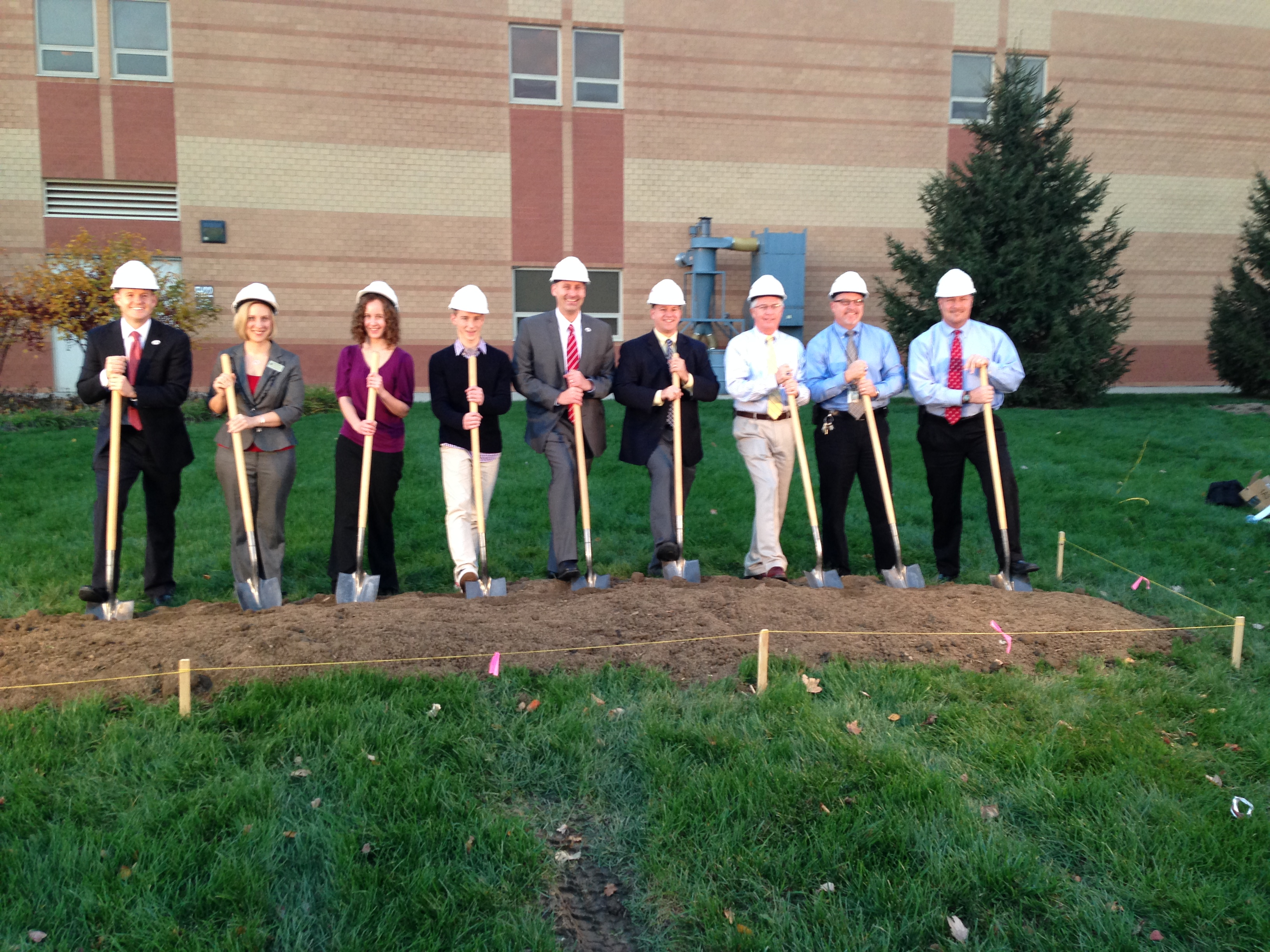 Fishers High School principal Jason Urban, 5th from left, breaks ground for the Senior Academy. He is joined by Fishers High School students and administrative staff. (Photo by Julie Roberts.)