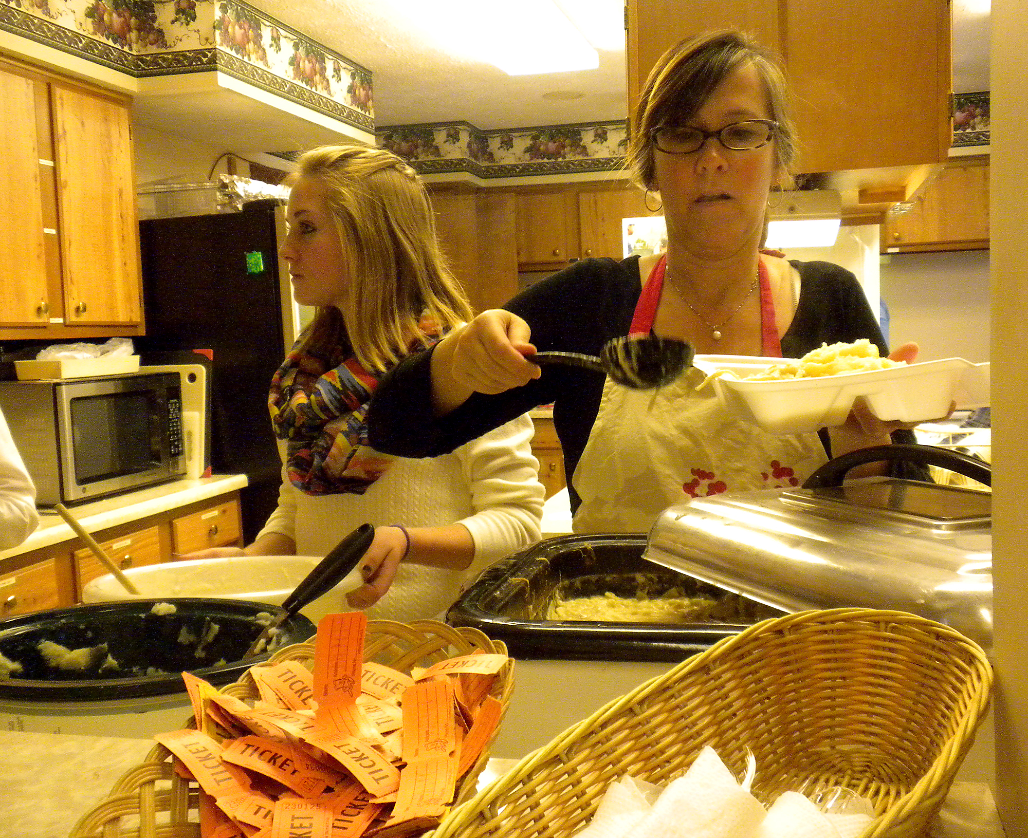 Westfield Friends Church members Jackie Hiatt and Jessica Thompson prepare a plate of chicken and noodles.