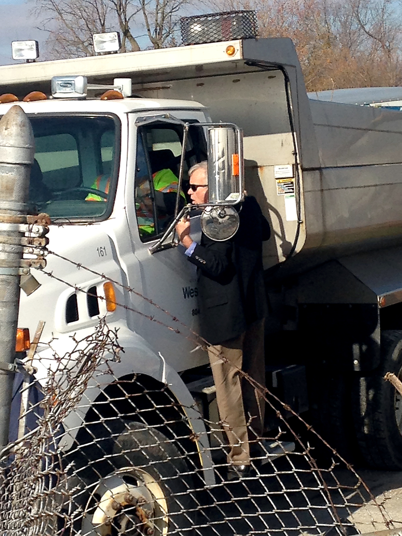 – Mayor Andy Cook talks with a Westfield public works employee as the city offered two dump trucks and a front loader to assist with storm cleanup.