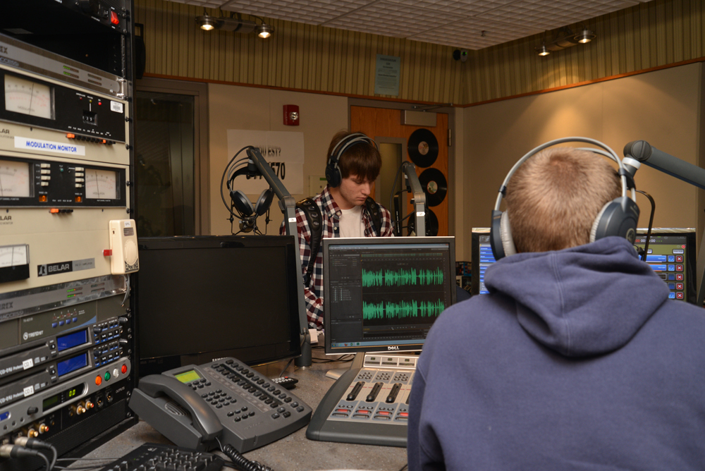 From left, Carmel High School students Grant Mullen and Jesse Smith work to broadcast the morning news and sports at WHJE. (Photo by Dawn Pearson)
