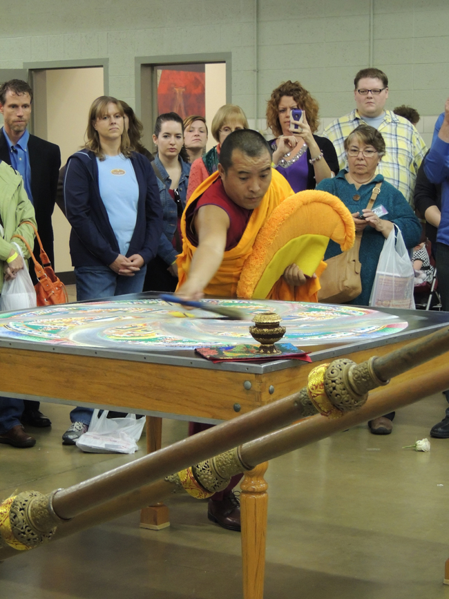 Gala Rinpcohe begins to dismantle the mandala sand painting. (Staff photo by Tonya Burton)