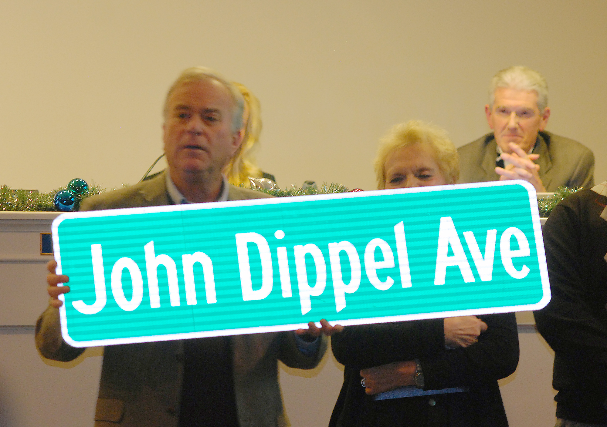 Mayor Andy Cook unveils the John Dippel Avenue sign that will be designated to a roadway in Westfield when an appropriate place has been determined. Dippel passed away on Sept. 21 while serving as a city council member.