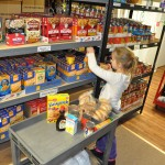 Bailey Oehler, 7, Natalie's daughter, helps fill up a cart. (Staff photo by Dawn Pearson)