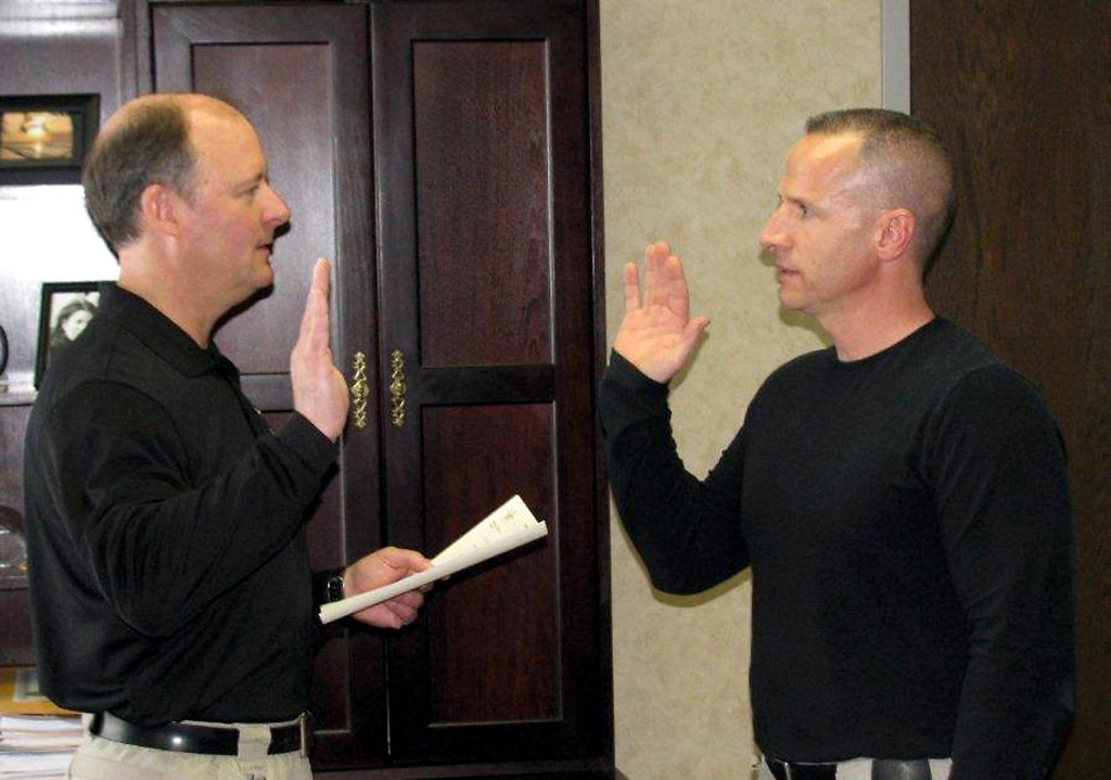 Sheriff Mark Bowen, left, administers the oath to Deputy John Cline, the newest addition to the patrol division, on Jan. 9. (Submitted photo)