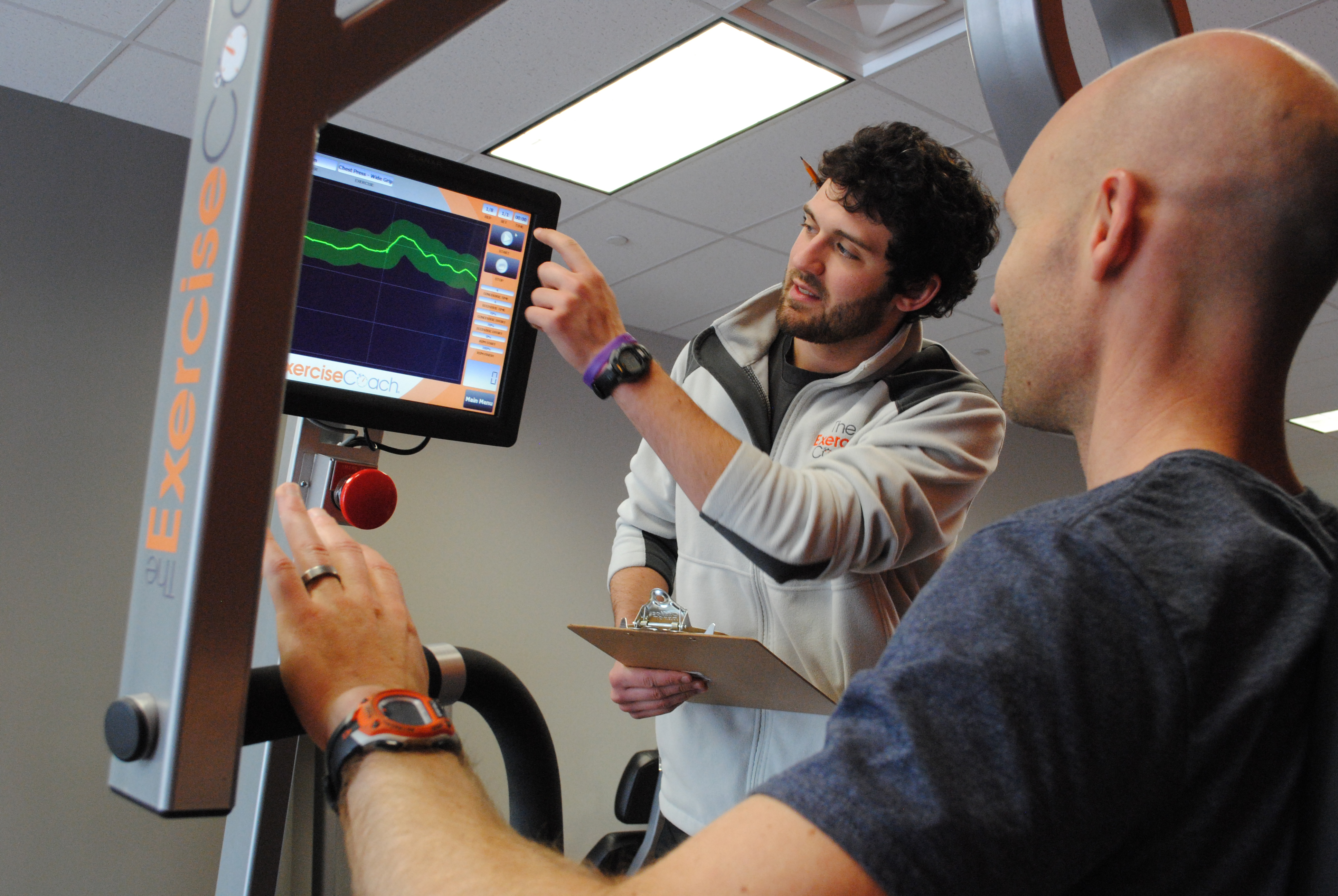 Trevor Junga, lead coach at The Exercise Coach, demonstrates a fitness graph on a bench press machine. (Staff photo)