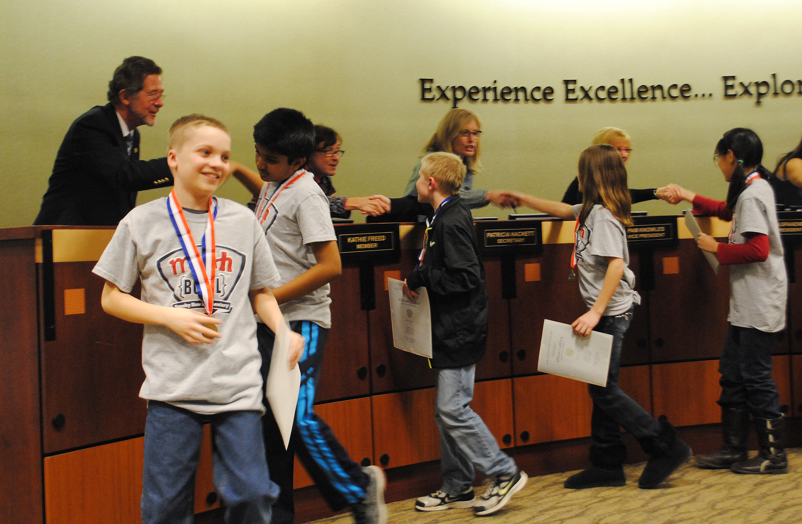 Smoky Row Elementary School students shake school board members' hands after being recognized for winning the state Math Bowl. (Staff photo)