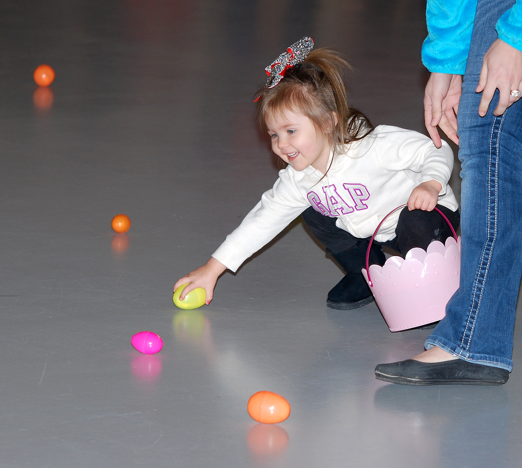 Paislee Tuell, 2, grabs an egg inside the Hamilton County 4-H Exhibition Center during last year's community egg hunt. (File photo)
