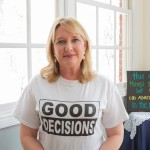 Dawn Finbloom wearing a T-shirt to promote the Lifeline Law. On the canvas behind her are lines from a poem Brett wrote before he passed away.