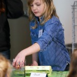 North Elementary School's Meg Gollner tests whether an egg is good or bad by putting it into a container of water.