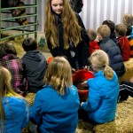 4-H'er Krista Standeford holds a bucket of horse feed for students to feel and smell.