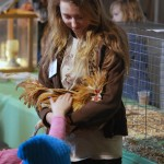 Annasty Mielke of Westfield High School holds her poultry project as students from Carmel's Mohawk Trails Elementary School pet the bird.