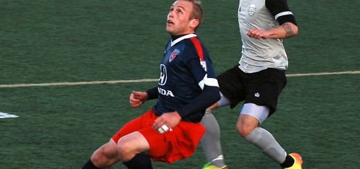 Indy Eleven defender Kyle Hyland controls a pass as Tourbeau player Lucas Almeida runs back on defense.
