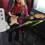 Eva Warren, 9, is learning to play guitar at School of Rock. (Staff photo by Adam Aasen)