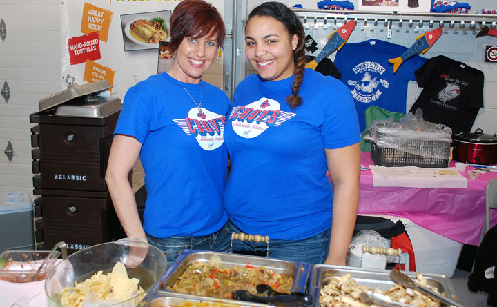 Bar manager Jewels Shrader, left, and server Chyanne Lopez provide nachos at the Chuy's booth during the Noblesville Chamber of Commerce Taste of Noblesville event on March 25. (Staff photo by Robert Herrington)