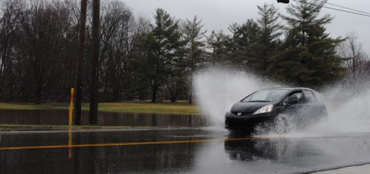 Cars drive through a flooded roadway at 126th Street in Carmel. (Staff photo)