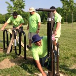 Hector Lopez, a member of the Facilities team at IU Health North Hospital and a Noblesville resident, puts the finishing touches on the newly installed bike maintenance station at Coxhall Gardens. Behind him, other members of the Facilities team install a bike rack. (Submitted photo)