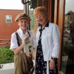 Michael Dick re-enacts a 1914 newsboy as he hands Library Foundation Director Ruth Nisenshal the latest paper during the 100th anniversary event. (Staff photo by Tonya Burton)