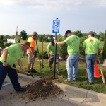 Jon Goble, president and CEO of IU Health North Hospital, shovels dirt as Chief Medical Officer Paul Calkins, MD, holds the post and is assisted by other IU Health team members during the IU Health Day of Service. (Submitted photo)
