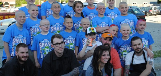Tatum stands in the center of the crowd of Shave-A-Thon participants as the barbers crouch in the front row. (Submitted photo)