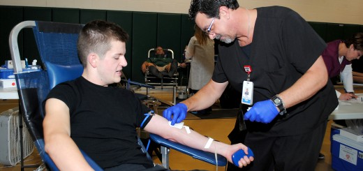 Jim Madewell of the Indiana Blood Center covers the needle in Westfield High School senior Corbin Atkins' arm as he donates to the Colts Leadership Challenge Blood Drive on July 16. (Photo by Robert Herrington)