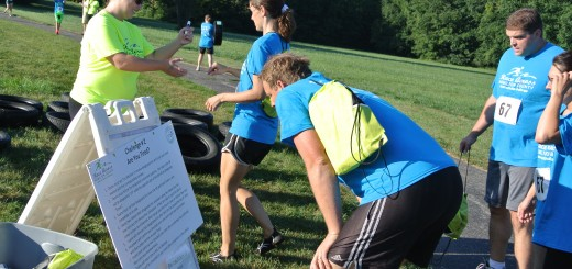 A volunteer from last year's Race Across Hamilton County stamps competitors' passports as they complete a challenge station.