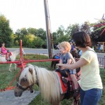 Young Elliott Koerner (foreground) was thrilled with the pony rides at CarmelFest KidZone. His mother, Wendy Koerner, assisted. (Staff photo by Tonya Burton)