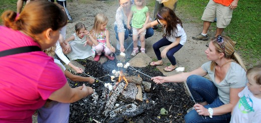 Parents and children roast marshmallows around the campfire at the close of the event.