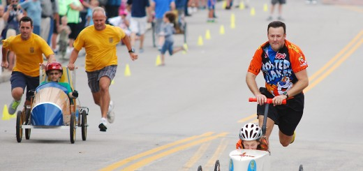 Tony Graf, right, pushes his daughter, Rachel, who was repeat champion last year, as Rotary Club members Mike Kearns and Ryan Rothaker push Mitch Boller. (File photo by Robert Herrington)