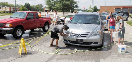 Band members work as fast as they can as vehicles line up around Ameriana Bank during the car wash.