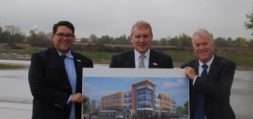 Cameron Orlean of Orlean Group, David Crisafi or Ceres Enterprises and Mayor Andy Cook hold a rendering of the planned Cambria Suites in front of where the hotel will be built in Grand Park. (Photo by Robert Herrington)