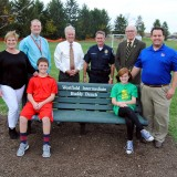 From left: Amy Lutz, Westfield Intermediate School Principal Corey Hartley, Colby Lutz, Mayor Andy Cook, Police Chief Joel Rush, Cate Lutz, Supt. Dr. Mark Keen and Matt Lutz un- veil the WIS Buddy Bench on Oct. 27. Each West- field elementary school will have one bench on its playground and the intermediate school has two. (Photo by Robert Herrington)