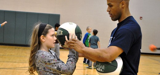 Eddie Gill helps Oak Trace Elementary student Roen Elbert properly position her hand on the basketball. (Submitted photo)