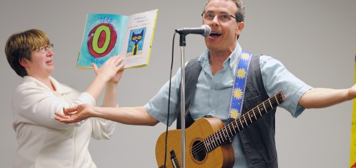 "Beth Anderson of Fishers turns the pages of ""Pete the Cat and His Four Groovy Buttons"" as author Eric Litwin sings the chorus with the crowd."