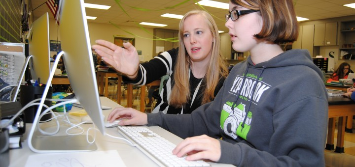 Allie Staub, left, talks with Westfield Middle School student Alicia Silhavy about her design in yearbook class. (Photo by Robert Herrington)