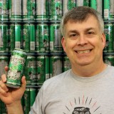 Sun King co-owner Dave Colt stands holding one of their craft beers, Fistfull of Hops. (Photo by James Feichtner)