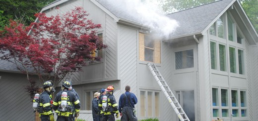 Firefighters watch the house that they use for practicing their drills as smoke created by a smoke machine comes out of the house. The smoke created by the machine is used to help simulate the limited visibility that a firefighter might have when going through a building that is burning.