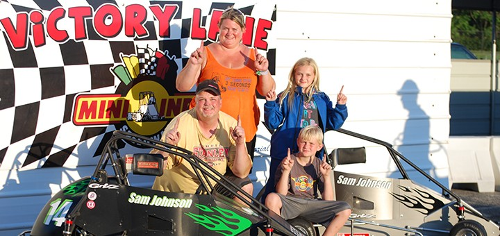 The Johnson family, Bill, Donita, Natalie, Sam, at Mini Indy Speedway after Sam won the feature races for both of the cars. (Photo by Leonard Foster)