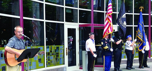 """Local musician Bruce McMahon leads the crowd in singing """"God Bless the U.S.A."""" at the flag ceremony June 14."""